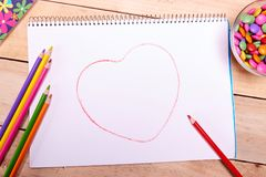 Leeg document, kleurrijke potloden en geassorteerd suikergoed op houten lijst stock foto