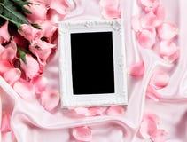 Leeg fotokader met een bloemblaadje van boeket zoet roze rozen op zachte roze zijdestof Stock Afbeeldingen