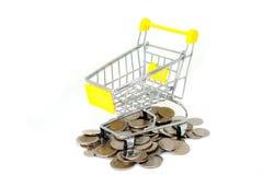 Leeg geel miniboodschappenwagentje of supermarktkarretje met stapel van zilveren geldmuntstukken Royalty-vrije Stock Fotografie