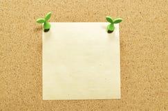 Leeg geel vierkant notadocument op cork raad met bladspeld Royalty-vrije Stock Foto