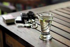Leeg geschoten glas op lijst met gelijken en sleutels op de achtergrond Stock Afbeeldingen