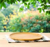 Leeg houten dienblad op lijst over achtergrond van het onduidelijk beeld de groene park, voedsel royalty-vrije stock afbeelding