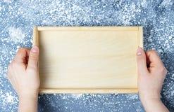 Leeg houten dienblad in vrouwelijke handen, hoogste mening, prototype royalty-vrije stock foto