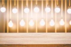 Leeg houten lijstbovenkant en onduidelijk beeld van Geel bollicht en bokeh binnen royalty-vrije stock afbeeldingen