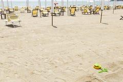 Leeg Italiaans strand met gele ligstoelen royalty-vrije stock afbeeldingen