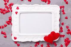 Leeg kader en vele decoratieve rode harten op geweven grijze bac Stock Foto
