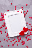 Leeg kader en vele decoratieve rode harten op geweven grijze bac Stock Foto's