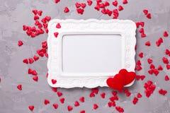 Leeg kader en vele decoratieve rode harten op geweven grijze bac Royalty-vrije Stock Afbeeldingen