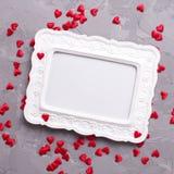 Leeg kader en vele kleine decoratieve rode harten op geweven g Stock Fotografie