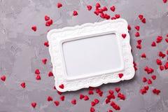 Leeg kader en vele kleine decoratieve rode harten op geweven g Stock Afbeelding