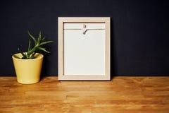 Leeg kader op een houten plank op een zwarte muur Stock Fotografie