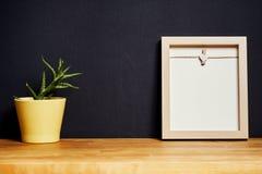 Leeg kader op een houten plank op een zwarte muur Royalty-vrije Stock Afbeeldingen