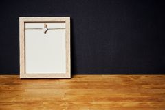 Leeg kader op een houten plank op een zwarte muur Royalty-vrije Stock Fotografie