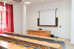Leeg klaslokaal met stoelen, bureaus en bord stock fotografie
