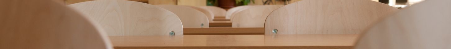 Leeg klaslokaal met stoelen en bureaus, breed panorama stock foto
