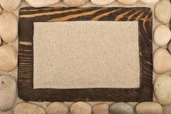 Leeg klassiek kader van donkere houten en witte stenen in het zand De ruimte van het exemplaar royalty-vrije stock fotografie