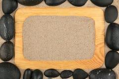 Leeg klassiek kader van lichte houten en zwarte stenen in het zand De ruimte van het exemplaar stock fotografie