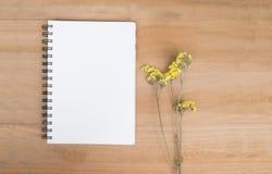 Leeg notaboek en gele bloemen houten achtergrond Mening van Royalty-vrije Stock Foto's