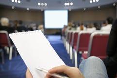 Leeg notitieboekje bij conferentiezaal. Stock Foto's