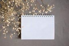 Leeg notitieboekje en droge bloem op grijze achtergrond De ruimte van het exemplaar stock fotografie