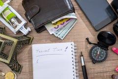 leeg notitieboekje met potlood, euro en dollar in portefeuille, kompas, zeeschelp, telefoon, de toren van Eiffel Stock Fotografie