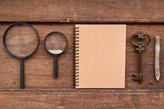 Leeg notitieboekje met potlood, sleutel en vergrootglas royalty-vrije stock afbeelding
