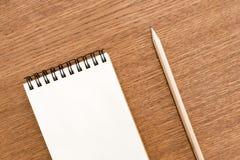 Leeg notitieboekje met spiraal voor de toepassing van etiketten en pen op houten achtergrond stock foto