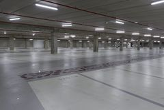 Leeg ondergronds parkeerterrein dat bij nacht wordt verlicht royalty-vrije stock afbeelding