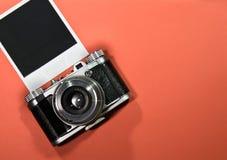 Leeg onmiddellijk fotokader op rode die achtergrond met oude retro uitstekende camera en exemplaarruimte wordt benadrukt Stock Fotografie