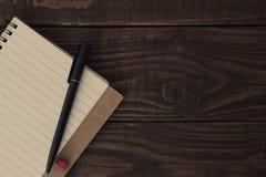 Leeg open notitieboekje met gevoerde documenten met pen op houten lijst Stock Fotografie