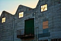 Leeg oud pakhuis met gebroken glas en golfmetaal Royalty-vrije Stock Foto
