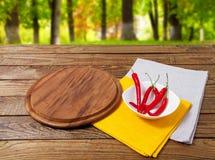 Leeg pizzabureau, roodgloeiende peper, geel en wit servet op houten lijst aangaande vage bosachtergrond royalty-vrije stock foto