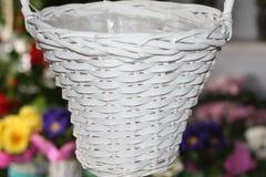Leeg rieten mand geschilderd wit op een bloemenachtergrond royalty-vrije stock foto