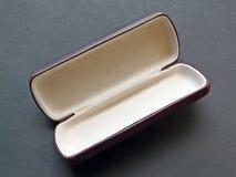 Leeg schouwspelgeval op een grijs stootkussen Stock Foto
