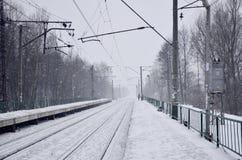 Leeg station in zware sneeuwval met dikke mist De spoorwegsporen gaan in een witte mist van sneeuw weg Het concept de spoorweg royalty-vrije stock fotografie