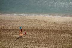 Leeg strand met slechts twee badmeesters Stock Foto's