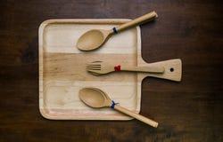 Leeg van houten die plaat met vork en lepel op houten donkere bruine lijst wordt geplaatst Stock Fotografie