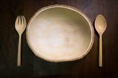 Leeg van houten die plaat met vork en lepel op houten donkere bruine lijst wordt geplaatst Stock Foto