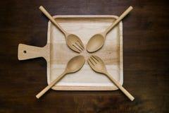 Leeg van houten die plaat met vork en lepel op houten donkere bruine lijst wordt geplaatst Royalty-vrije Stock Afbeelding