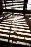 Leeg wijnglas en mooie schaduwen van zonneblinden op venster Royalty-vrije Stock Fotografie