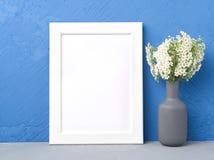 Leeg wit kader, bloem in vaze op grijze lijst tegen donkerblauwe concrete muur met exemplaarruimte Spot omhoog Royalty-vrije Stock Afbeeldingen