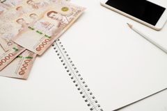 Leeg wit spiraalvormig notitieboekje met wit potlood, mobiele telefoon en stapel van nieuwe 1000 Thaise Bahtbankbiljetten royalty-vrije stock foto