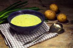 Leek cream soup with fresh spring onions and potatoes on rustic. Bowl with leek cream soup, fresh spring onions and potatoes on a rustic wooden table Stock Photos