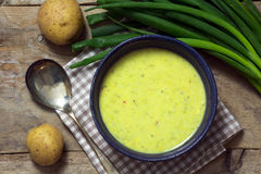 Leek cream soup with spring onions and potatoes on rustic wood. Leek cream soup with spring onions and potatoes on a rustic wooden table, view from above Stock Image