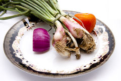 Leek onions and onion with tomato on plate. And on white background Royalty Free Stock Photo