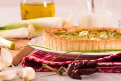 Leek quiche. Leek quiche with sour cream on white dish stock photos