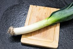 leek ready to be cut and cooked. Leek on a wooden cutting board royalty free stock photo