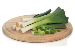 Leeks. Whole and chopped on a wooden bread board, isolated over white background stock image
