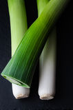 Leeks Arranged on Black Royalty Free Stock Image