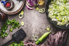 Leeks meal eating and cooking . Pan with sliced leeks on kitchen table background with tools and ingredients, top view. Frame Royalty Free Stock Images